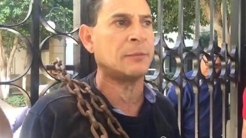 Bombero se encadena para exigir pago de días festivos