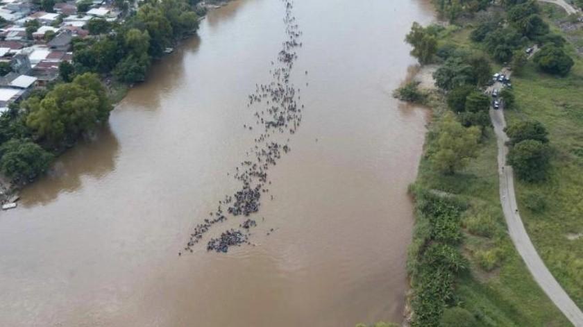 Decenas de migrantes de una tercera caravana cruzan el río Suchiate hacia México