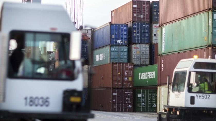 Esta foto de archivo del 5 de julio del 2018 muestra a dos camiones en un lote de contenedores del puerto de Savannah, Georgia.(AP)