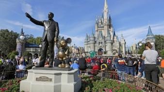 Visitantes viendo una presentación cerca de la estatua de Walt Disney y Mickey Mouse frente al castillo de la Cenicienta en el Magic Kingdom de Walt Disney World en Lake Buena Vista, Orlando, Florida.