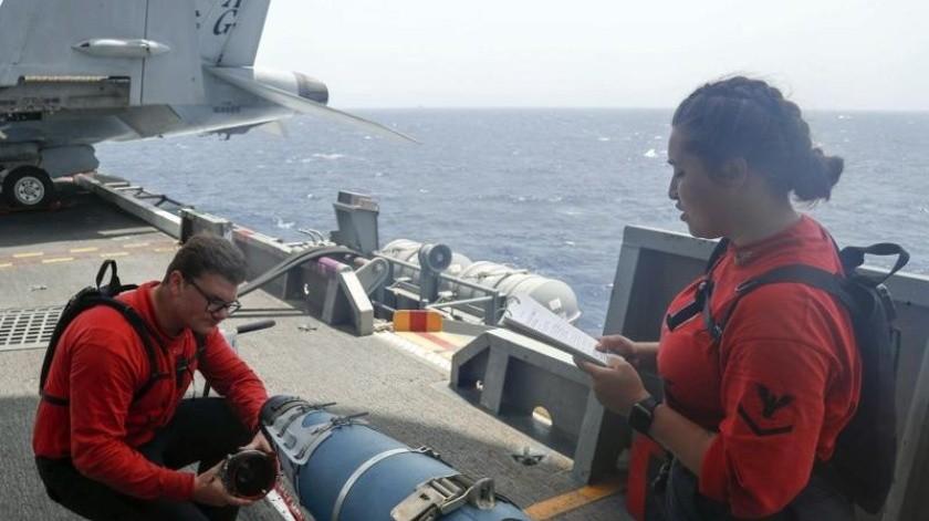 En esta imagen, tomada el 15 de mayo de 2019 y distribuida por la Marina de Estados Unidos, dos militares inspeccionan un proyectil a bordo del USS Abraham Lincoln en el Mar Arábigo(AP)