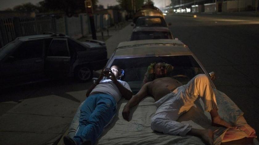 Dos hombres venezolanos esperan montados sobre un vehículo en una cola para conseguir gasolina en Cabimas.(AP)
