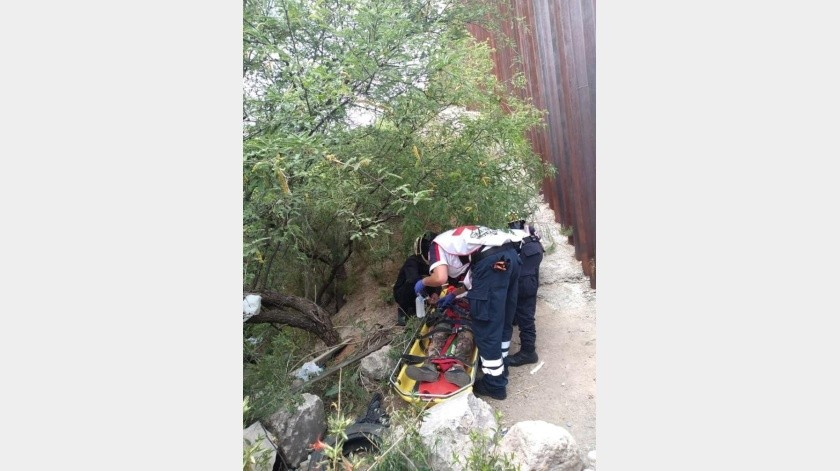 Una joven migrante que intentaba cruzar de manera ilegal hacia Estados Unidos cayó desde lo alto de la barda hacia un barranco y fue rescatada lesionada por grupos de auxilio para luego ser hospitalizada.