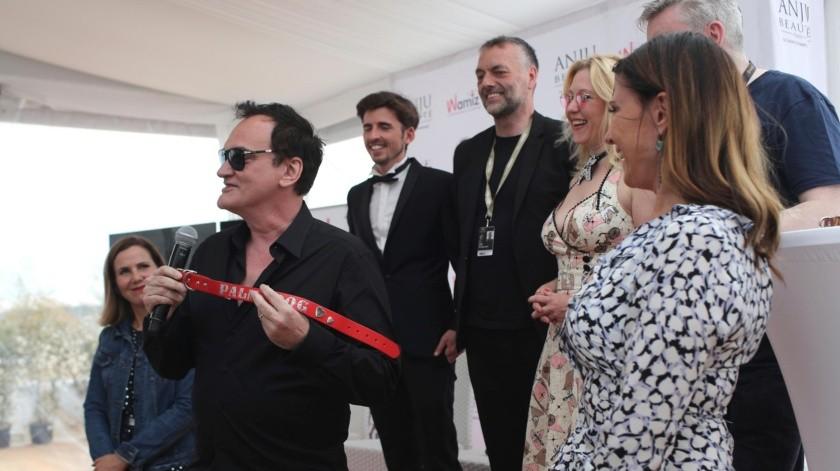 Tarantino sorprendió al público el viernes cuando acudió en persona a recibir su trofeo: un collar de perro rojo. Vitoreó a la perrita Brandy, la pit bull del personaje de Brad Pitt en el filme.(AP)
