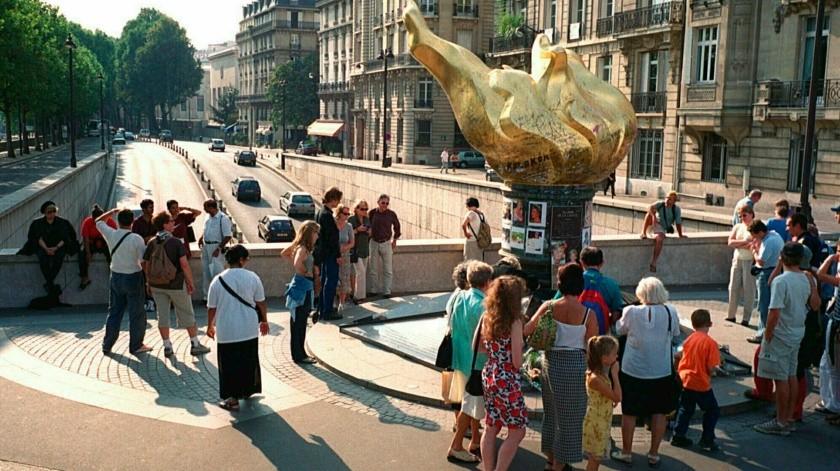 Gente alrededor de una estatua modelada como la llama de la Estatua de la Libertad, que sirve como monumento no oficial para la princesa Diana sobre el túnel donde murió tres años antes, en París.(AP)