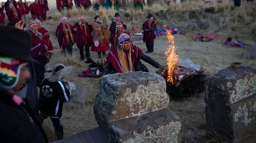 Un hombre aymara derrama la sangre de una llama recién sacrificada durante una ofrenda para recibir los primeros rayos de luz solar en un ritual de Año Nuevo en las ruinas de Lukurmata, Bolivia.(AP)