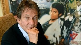 El abogado del entretenimiento John Branca, coalbacea de la herencia de Michael Jackson, posa en su oficina junto a una obra que recibió de Sony Music por la venta de 100 millones de copias del álbum