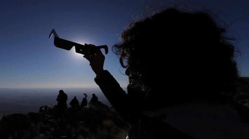 Una persona mira sus anteojos especiales durante el Eclipse solar total, este martes en la ciudad de Merlo, San Luis (Argentina).(EFE)
