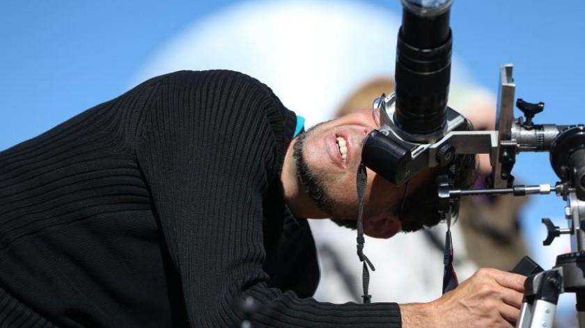Un hombre observa el sol a través de su cámara fotográfica horas antes de que comience el eclipse solar total, este martes en el Observatorio de La Silla, situado en la región de Coquimbo (Chile).(EFE)