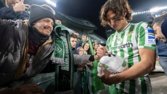 Diego Lainez firmando souvenirs a aficionados de Betis en su presentación.