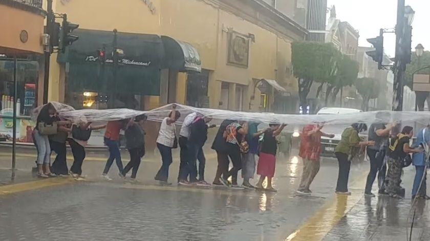 VIDEO: Con hule y fila india se protegen de la lluvia(Captura de video)