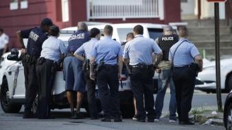 Varios policías de Filadelfia se resguardan detrás de un vehículo durante un tiroteo en el vecindario Nicetown de Filadelfia.
