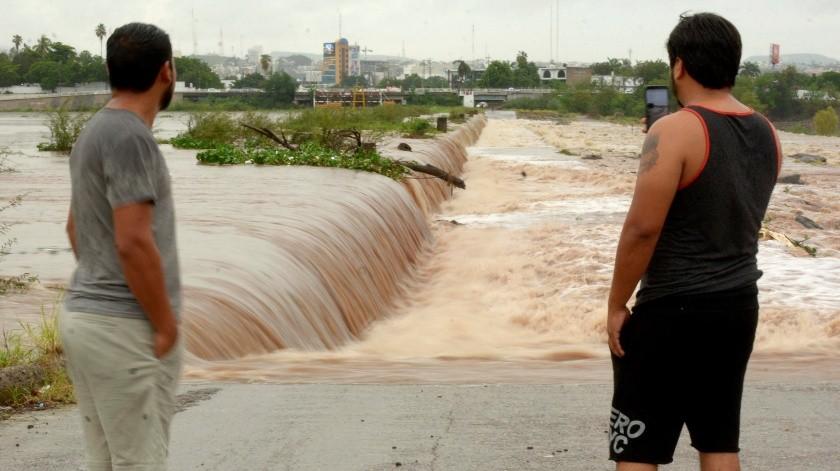 Dos hombres observan el alto caudal de un río por las constantes lluvias que la tormenta Evo está dejando en el estado de Sinaloa (México).(EFE)