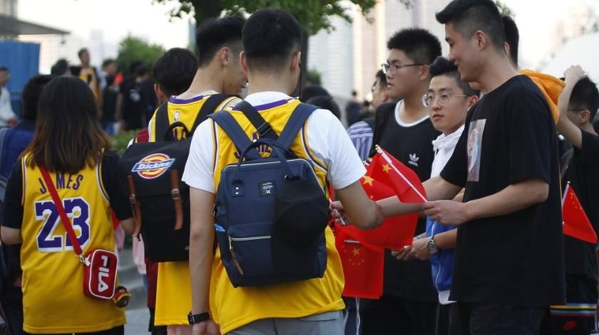 Los fanáticos entregan banderas nacionales chinas a otros que llegan para el juego de pretemporada de la NBA que se llevará a cabo en el Mercedes Benz Arena en Shanghai, China.(AP)