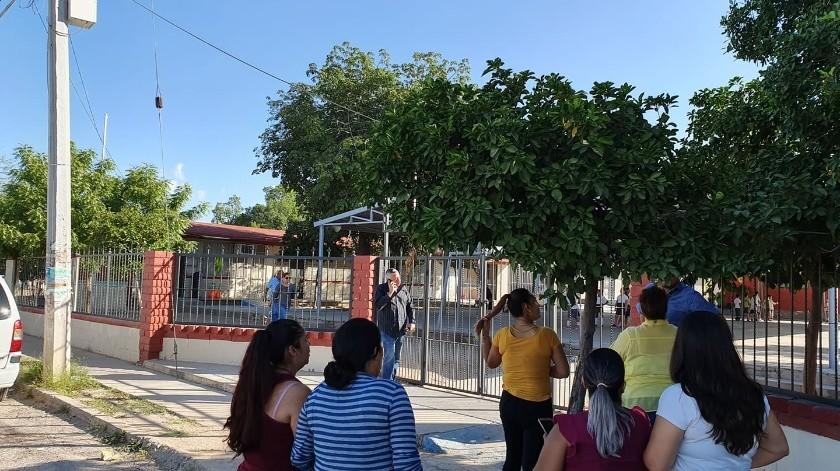 Alumnos cargan mesabancos de un salón a otro por falta de espacio; padres se manifiestan(Mirna Lucía Robles)