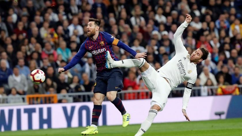 El defensa del Real Madrid Sergio Ramos (d) lucha con el argentino Leo Messi, del FC Barcelona, durante un partido.(EFE)