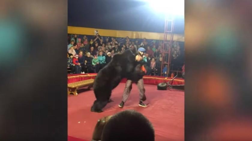 El domador cayó al suelo mientras el oso lo atacabay otra persona lo pateaban en su intento porque soltara al hombre.