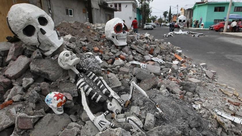 Decoran calles con calaveras enterradas; aprovechan baches(EFE)