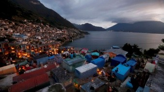 Lugareños adornan este viernes con flores y velas la tumbas del cementerio a la orilla del lago de Atitlán, en San Antonio Palopo, Guatemala.