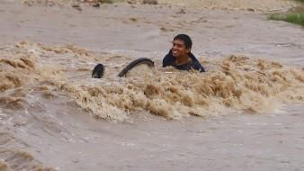 José Rodríguez intentó cruzar en bicicleta el arroyo crecido de la colonia Laura Alicia Frías de López Nogales, en Hermosillo, y se lo llevó la corriente por unos momentos.