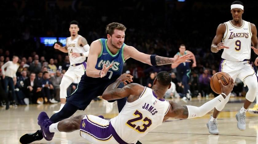 LeBron James recupera un balón perdido para los Lakers debajo de Luka Doncic de los Lakers en el triunfo de los Mavericks de Dallas sobre Los Ángeles del domingo primero de diciembre del 2019.(AP)