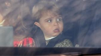 El príncipe Luis viaja en el asiento trasero de un auto conducido por su madre Kate, al arribar al Palacio de Buckingham para el almuerzo tradicional de la reina.
