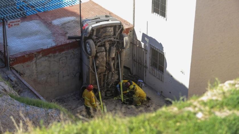 Al caer, el automóvil quedó de forma frontal, sobre el capacete recargado en la barda de uno de los inmuebles.(Gustavo Suárez)