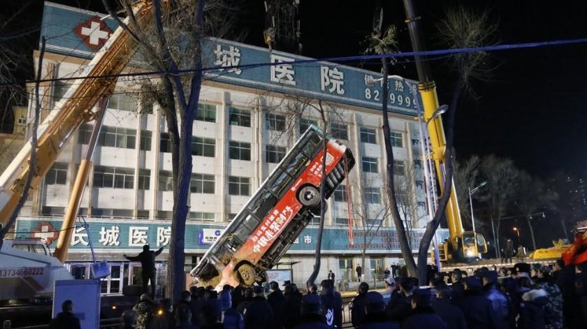 En esta imagen tomada del video de CCTV, un autobús se hunde en un sumidero en el centro de una calle del centro, el lunes 13 de febrero de 2020, en Xining, provincia de Qinghai, China.(AP)