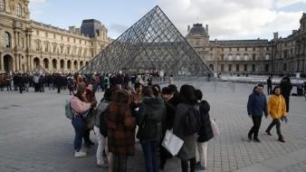 Turistas esperan y empleados en huelga se manifiestan en la entrada al Museo del Louvre, París.