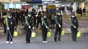 Empleados rocían una solución antiséptica en el aeropuerto internacional en Incheon, Corea del Sur.