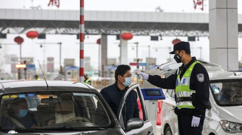 Policía usa un termómetro digital en un punto de peajes en una carretera en Wuhan, en el centro de China.