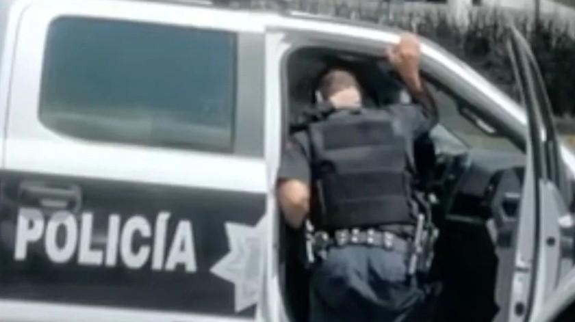 En una grabación de 34 segundos difundida en redes sociales se exhibió a policías de Zapopan, Jalisco, quienes estando de servicio se mostraron cariño de forma física.(Captura de video)