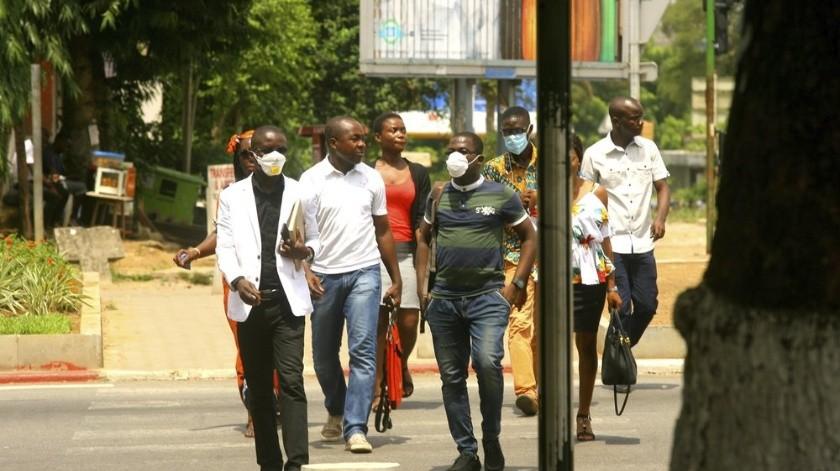 En esta fotografía tomada el jueves 19 de marzo de 2020, los residentes de Abidjan, Costa de Marfil, usan máscaras para protegerse del coronavirus mientras caminan por una calle.(AP)