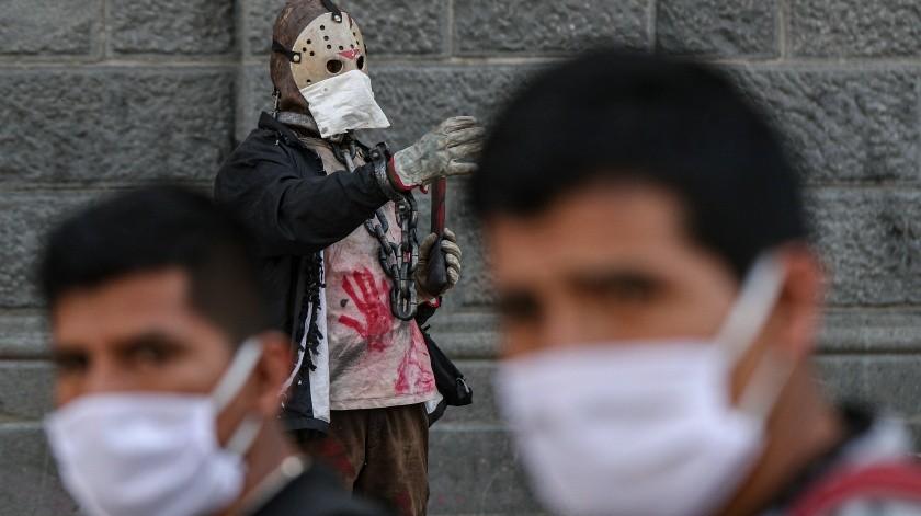 """Un artista callejero vestido como Jason, personaje de la película """"Viernes 13"""", usa mascarilla como precaución ante la propagación del coronavirus, en el centro de Santiago, Chile.(AP)"""