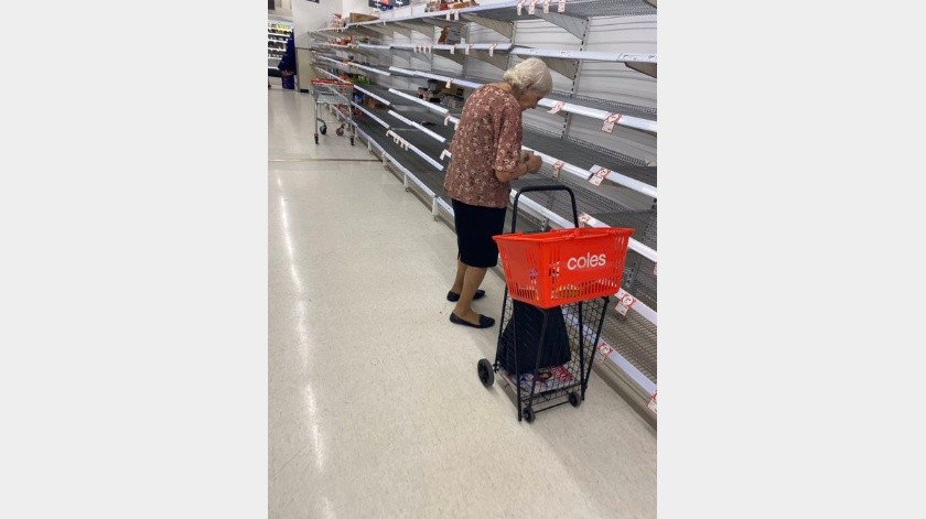 """na señora de la tercera edad frente a anaqueles vacíos del súper """"Coles"""", en el puerto de Melbourne, Australia(Cuenta Oficial de Twitter de Sebastian Costello @SebCostello9)"""