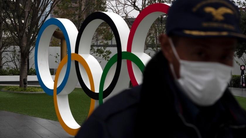 Un guardia de seguridad camina frente a los anillos olímpicos cerca del Estadio Nacional de Tokio, el lunes 23 de marzo de 2020.(AP)
