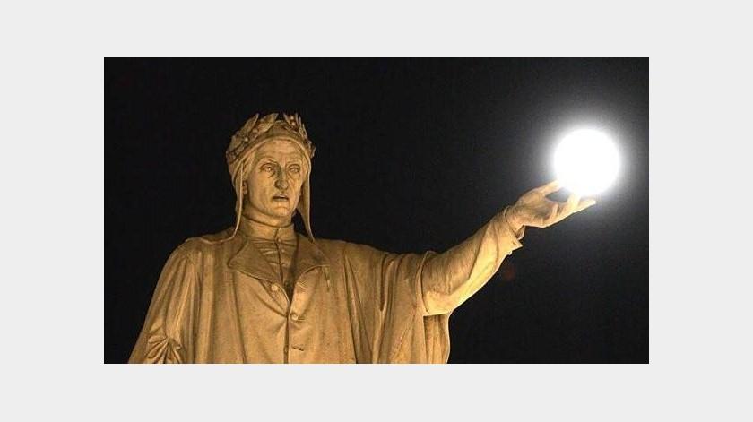"""La luna llena """"se posa"""" sobre la mano de la estatua que tiene el afamado poeta en Nápoles.(EFE)"""