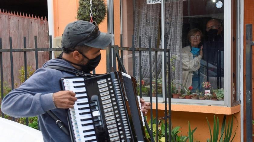 Toca el acordeón frente a la ventana de sus padres para animarlos en la cuarentena(Jose Luis Saavedra / Reuters)