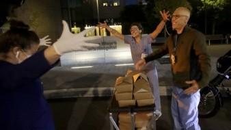 El chef y dueño del restaurante NightBird de San Francisco, Kim Alter, abraza de lejos a los enfermeros Sydney Gressel, Matt Phillips al entregarles cenas en el Hospital Pediátrico Benioff en San Francisco.