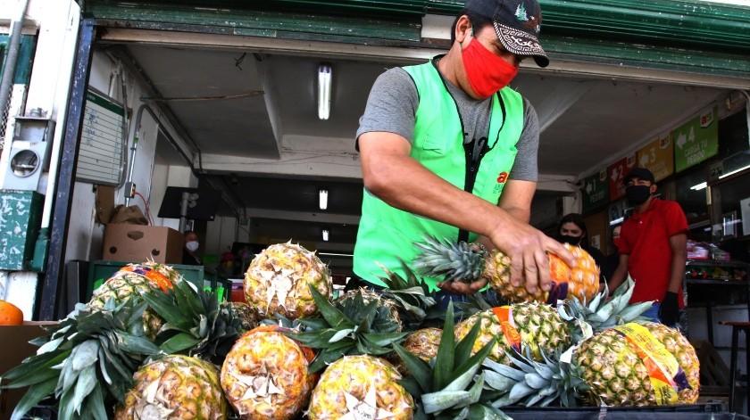 Francisco Javier Alonso acomoda las piñas en el puesto ubicado en el Mercado de Abastos Francisco I. Madero.(Julián Ortega)
