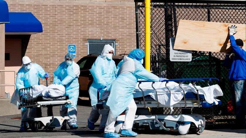 Los trabajadores de la salud transportan dos cuerpos más allá de un trabajador de la construcción que construye el interior de una de las dos morgues temporales establecidas fuera del Centro Médico Wyckoff Heights para manejar la gran cantidad de víctimas de la enfermedad COVID-19 en Brooklyn, Nueva York, EE. UU(EFE)