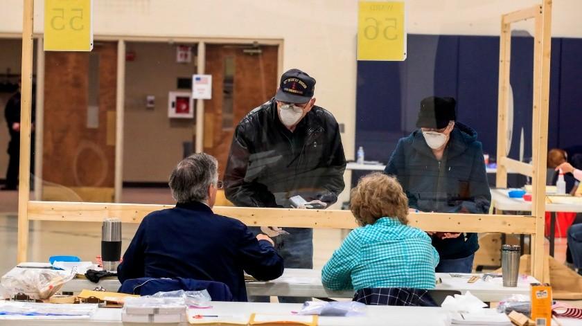 Los trabajadores electorales se sientan detrás de las sábanas de plástico mientras registran a los votantes en la Iglesia Bíblica de Kenosha en Kenosha, Wisconsin, EE. UU..(EFE)