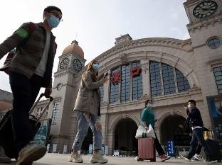 Viajeros con maletas caminan frente a la estación ferorviaria de Hankou cuando se apresta a reanudar el tráfico desde Wuhan, China, hacia afuera de la ciudad.