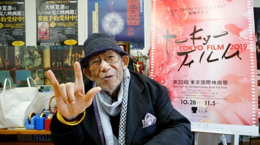 """El director japonés Nobuhiko Obayashi haciendo la señal de """"Te amo"""" para enfatizar que es un mensaje importante en sus películas, durante una entrevista en su estudio en Tokio.(AP)"""