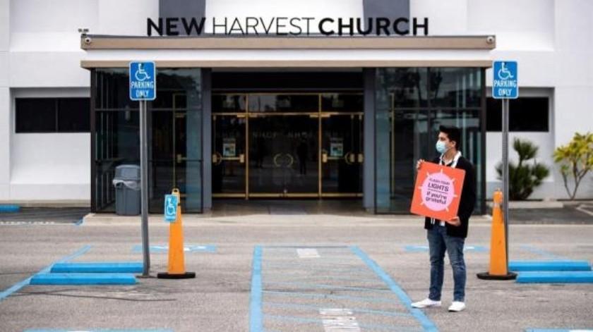 """Un voluntario da la bienvenida a los autos de los feligreses con un cartel que dice """"Enciende las luces si estás agradecido"""" durante una misa de Pascua en la Iglesia New Harvest en medio de la pandemia de coronavirus en Norwalk, al sur de Los Ángeles, California(EFE)"""