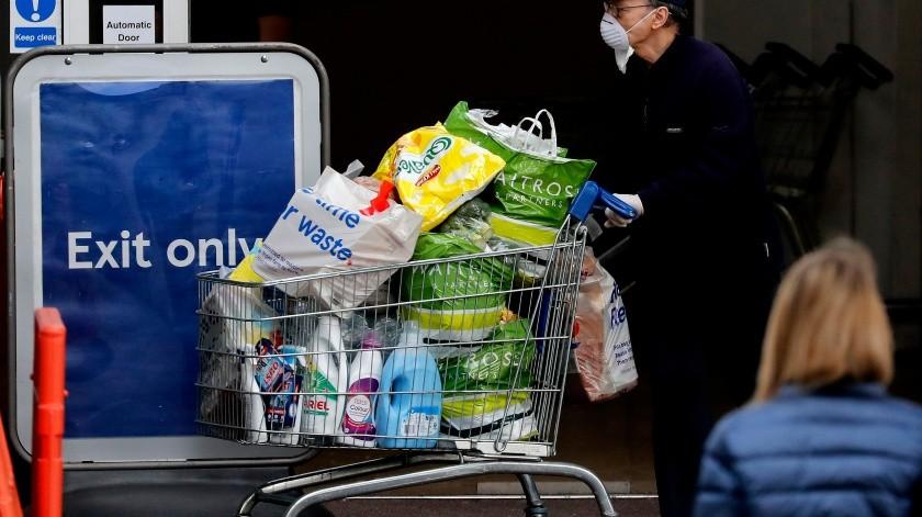 Un hombre, con mascarilla para protegerse del coronavirus, sale de un supermercado con un carro de la compra lleno, en Londres, el 17 de abril de 2020.(AP)