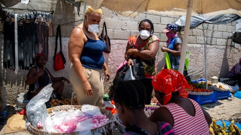 Pocas mujeres lucen tapabocas en esta escena del 15 de abril del 2020 en un mercado callejero de Puerto Príncipe, Haití.(AP)
