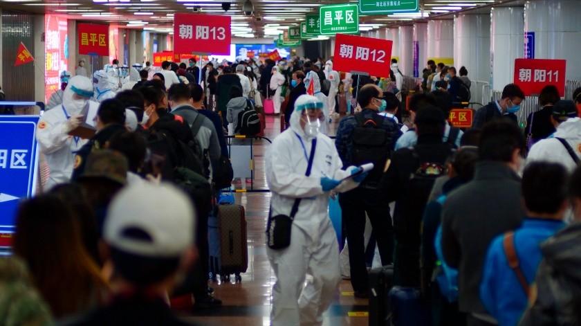 Pasajeros de Wuhan esperan en filas que señalan donde realizarán una cuarentena en Beijing, China, el 15 de abril de 2020.(AP)