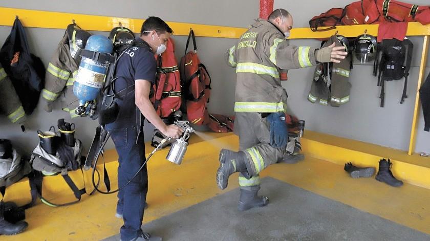 El bombero Marco Antonio Trujillo muestra este equipo modificado, con una pistola de pintar, que también sirve para sanitizar al personal cuando entran y salen de un servicio o turno.(Teodoro Borbón)