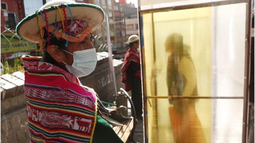 """En medio de un mercado de Bolivia, una larga fila de personas espera su turno para entrar a una cabina de desinfección donde se darán un """"baño de vapor""""(AP)"""